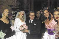 Yves Saint-Laurent obklopen modelkami. Ve svatebních šatech jeho favoritka Claudia Schifferová. - foto Corbis Sygma